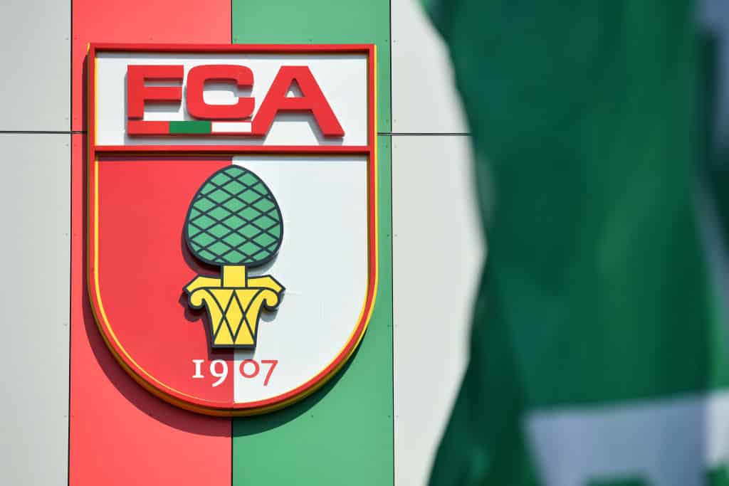 AUGSBURG, GERMANY - MAY 16: General view of the logo of FC Augsburg outside the WWK-Arena while ahead of the Bundesliga match between FC Augsburg and VFL Wolfsburg takes place on May 16, 2020 in Augsburg, Germany. The Bundesliga and Second Bundesliga is the first professional league to resume the season after the nationwide lockdown due to the ongoing Coronavirus (COVID-19) pandemic. All matches until the end of the season will be played behind closed doors. (Photo by Sebastian Widmann/Getty Images)