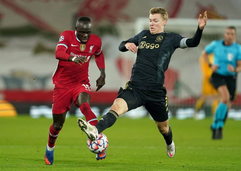 LIVERPOOL, ENGLAND - DECEMBER 01: Sadio Mane of Liverpool is challenged by Perr Schuurs of Ajax during the UEFA Champions League Group D stage match between Liverpool FC and Ajax Amsterdam at Anfield on December 01, 2020 in Liverpool, England. Sporting stadiums around the UK remain under strict restrictions due to the Coronavirus Pandemic as Government social distancing laws prohibit fans inside venues resulting in games being played behind closed doors. (Photo by Jon Super - Pool/Getty Images)